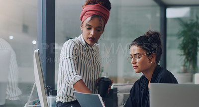 Buy stock photo Cropped shot of two attractive young businesswomen working together in the office