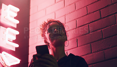 Buy stock photo Shot of a young woman using her cellphone while outside a building at night