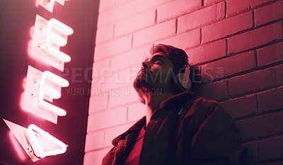 Buy stock photo Shot of a young man wearing headphones while leaning against a building at nighttime