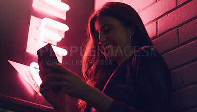 Buy stock photo Shot of a young woman using her cellphone while standing  outside a building at night