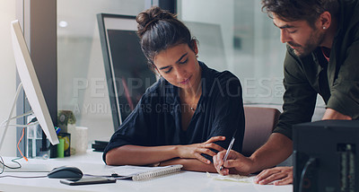 Buy stock photo Cropped shot of two young businesspeople working together in the office
