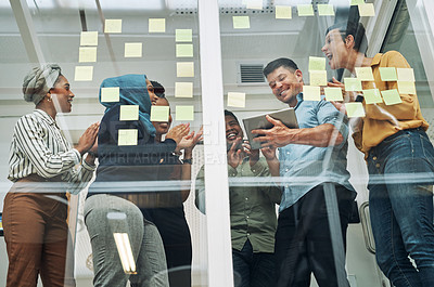 Buy stock photo Shot of a group of businesspeople applauding a colleague while brainstorming on a glass wall in an office