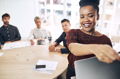 Buy stock photo Shot of a young businesswoman using a laptop while giving a presentation to her colleagues in an office