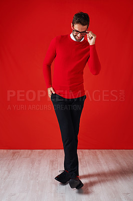 Buy stock photo Studio shot of a handsome and stylish young man posing with his hand in his pocket against a red background