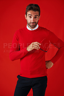Buy stock photo Studio portrait of a handsome and stylish young man posing with his hand on his hip against a red background