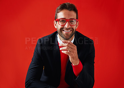 Buy stock photo Studio portrait of a handsome and stylish young man against a red background