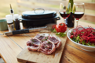 Buy stock photo Shot of red meat and other cooking items on a chopping board at a barbecue