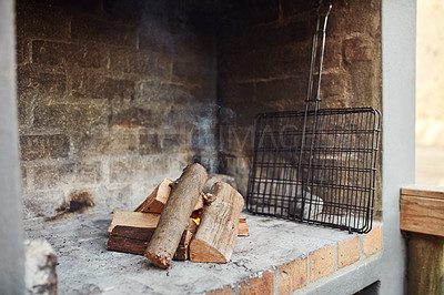Buy stock photo Shot of a log fire in an outdoor fireplace at home
