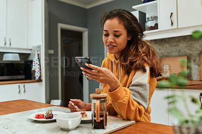 Buy stock photo Shot of a young woman using her cellphone while having breakfast at home