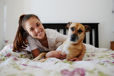 Buy stock photo Shot of a young woman relaxing in bed with her dog