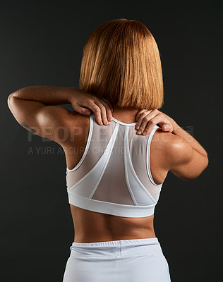 Buy stock photo Rearview shot of a woman wearing sports clothing against a dark background
