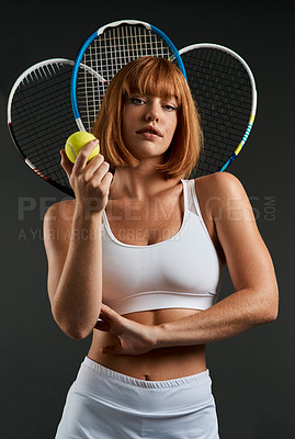 Buy stock photo Cropped shot of a woman posing with a tennis racket and ball against a dark background