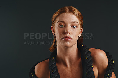 Buy stock photo Studio portrait of a sporty young woman posing with a battle rope against a black background