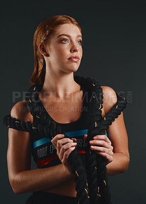 Buy stock photo Studio shot of a sporty young woman posing with a battle rope against a black background