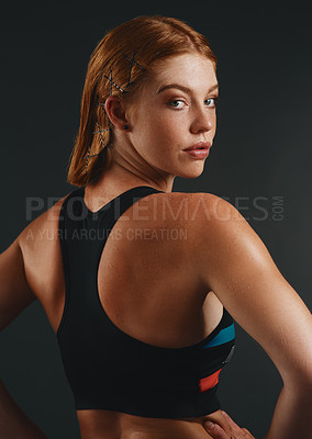 Buy stock photo Studio portrait of a sporty young woman posing against a black background
