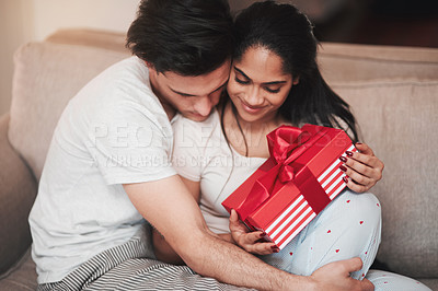 Buy stock photo Cropped shot of a handsome young man hugging his girlfriend on the living room sofa on her birthday