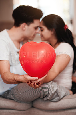 Buy stock photo Cropped shot of an unrecognizable young couple kissing while holding a heart-shaped balloon on valentine's day