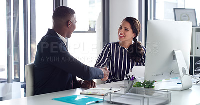 Buy stock photo Shot of two businesspeople shaking hands while working together on a computer in an office