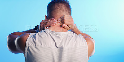 Buy stock photo Rearview shot of an unrecognizable young man rubbing his neck in pain against a blue background
