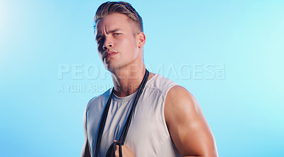 Buy stock photo Studio portrait of a young man posing with a skipping rope against a blue background
