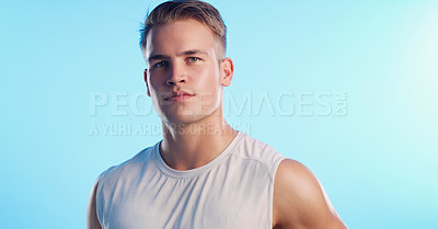 Buy stock photo Studio portrait of a handsome young man posing against a blue background