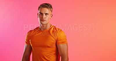 Buy stock photo Studio portrait of a handsome young man posing against a peach background