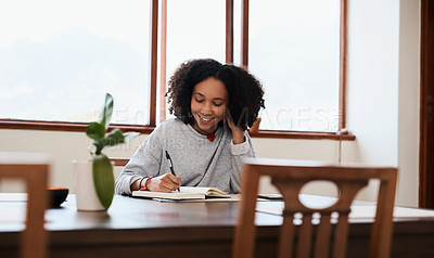 Buy stock photo Shot of a young woman writing in a notebook while working at home
