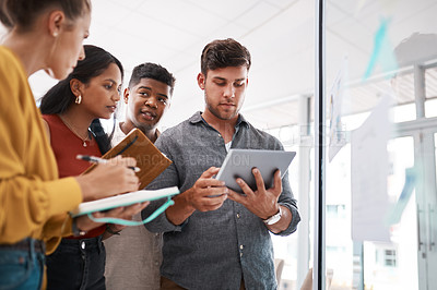 Buy stock photo Shot of a group of businesspeople using a digital tablet while brainstorming on a glass wall in an office