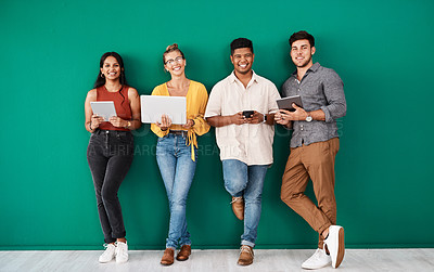Buy stock photo Portrait of a group of young designers using digital devices while standing together against a green background
