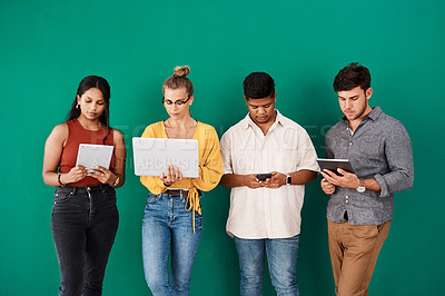 Buy stock photo Shot of a group of young designers using digital devices while standing together against a green background