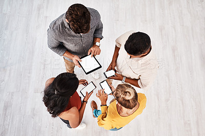 Buy stock photo High angle shot of a group of young designers using digital devices in synchronicity in an office