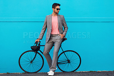 Buy stock photo Shot of a handsome young man posing with his bicycle against a blue wall in the city