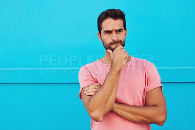 Buy stock photo Shot of a handsome young man looking thoughtful against a blue wall