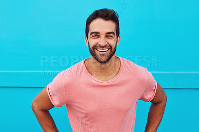Buy stock photo Shot of a handsome young man posing against a blue wall