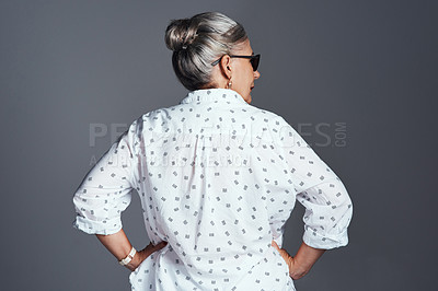 Buy stock photo Rearview shot of a senior woman wearing sunglasses while posing against a grey background