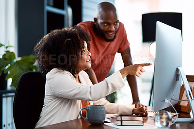 Buy stock photo Shot of two young designers looking at something on a computer screen