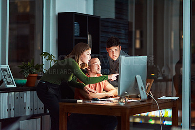 Buy stock photo Shot of a group of designers looking at something on a computer while working late