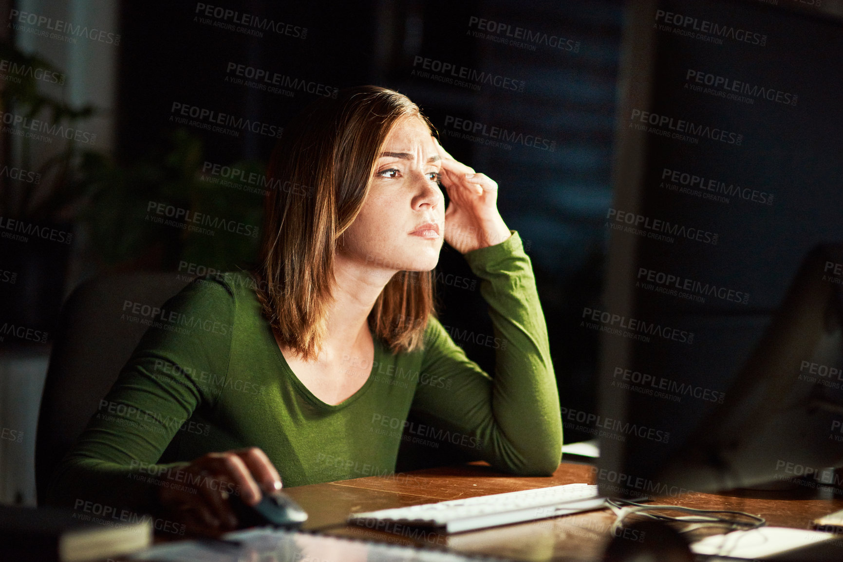 Buy stock photo Cropped shot of a young woman using her computer while working late