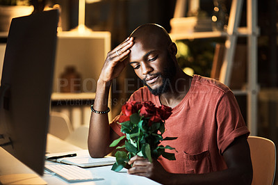 Buy stock photo Shot of a businessman looking at a bunch of roses while working late at the office