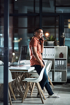 Buy stock photo Shot of a businessman talking on his cellphone while working late at the office