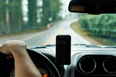 Buy stock photo Cropped shot of a man using his phone's gps system while driving a car
