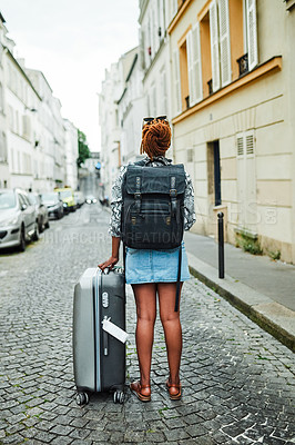 Buy stock photo Rearview shot of a young woman standing with her luggage in an alleyway in Paris, France