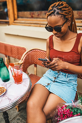Buy stock photo Shot of an attractive young woman using her cellphone while relaxing at an outdoor cafe in Paris, France