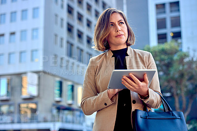 Buy stock photo Cropped shot of a businesswoman using a digital tablet while out in the city