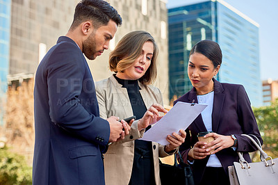 Buy stock photo Shot of three businesspeople having a discussion while looking at a document