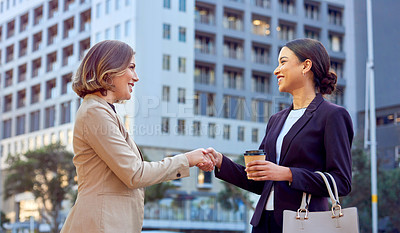 Buy stock photo Shot of two businesswomen shaking hands while standing outdoors