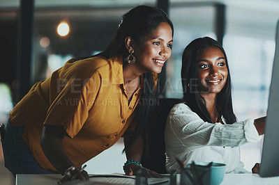 Buy stock photo Shot of two young businesswomen working together on a computer in an office at night