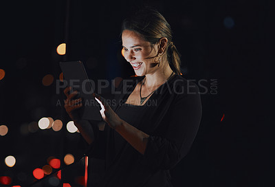 Buy stock photo Shot of a young businesswoman using a digital tablet outside an office at night