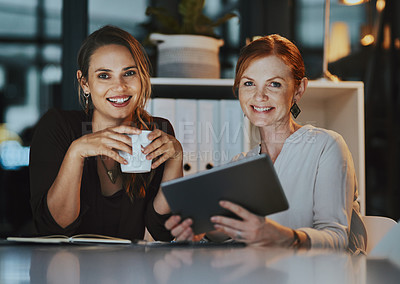 Buy stock photo Portrait of two businesswomen using a digital tablet together in an office at night