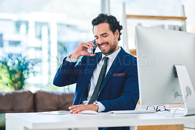 Buy stock photo Shot of a young businessman talking on a cellphone while working on a digital tablet in an office